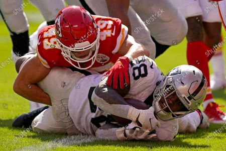 Las Vegas Raiders running back Josh Jacobs (28) is tackled in the end zone by Kansas City Chiefs safety Daniel Sorensen (49) to score a touchdown during the second half of an NFL football game, in Kansas City, Mo. The Raiders won 40-32