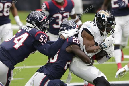 Jacksonville Jaguars running back Chris Thompson (34) is wrapped up by Houston Texans defensive back Michael Thomas (28) during the first half of an NFL football game, in Houston