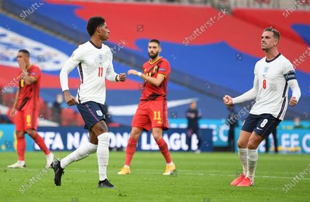 England's Marcus Rashford, left, celebrates with England's Jordan Henderson after scoring his side's first goal from the penalty spot during the UEFA Nations League soccer match between England and Belgium at Wembley stadium in London