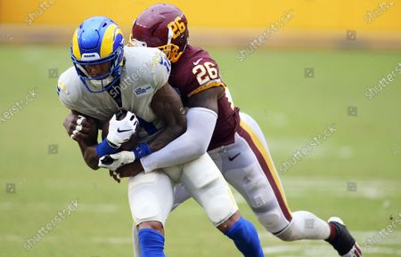 Washington Football Team strong safety Landon Collins (26) takes down Los Angeles Rams wide receiver Josh Reynolds (11) during an NFL game against the Los Angeles Rams, in Landover, Md