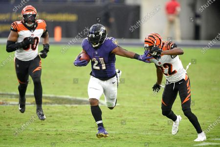 Baltimore Ravens running back Mark Ingram (21) runs with the ball as Cincinnati Bengals cornerback William Jackson (22) tries to stop him during the second half of an NFL football game, in Baltimore