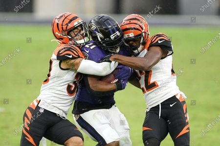 Baltimore Ravens running back Mark Ingram, center, is hit by Cincinnati Bengals free safety Jessie Bates, left, and cornerback William Jackson during the second half of an NFL football game, in Baltimore