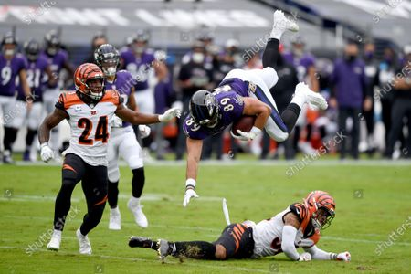 Baltimore Ravens tight end Mark Andrews (89) is upended by Cincinnati Bengals free safety Jessie Bates, right, after making a catch during the first half of an NFL football game, in Baltimore
