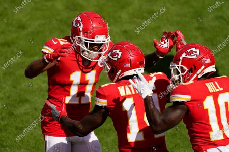 Kansas City Chiefs wide receiver Sammy Watkins, center, celebrates with teammates Demarcus Robinson, left, and Tyreek Hill, right, after catching an 8-yard touchdown pass during the first half of an NFL football game against the Las Vegas Raiders, in Kansas City