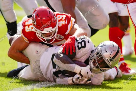Las Vegas Raiders running back Josh Jacobs scores on a 7-yard touchdown run ahead of Kansas City Chiefs safety Daniel Sorensen (49) during the second half of an NFL football game, in Kansas City