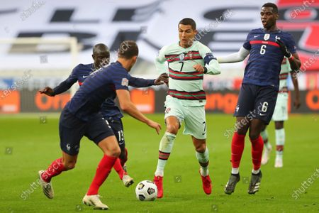 Portugal's Cristiano Ronaldo, center, runs with the ball at France's Benjamin Pavard, foreground, between Ngolo Kante and Paul Pogba, right, during the UEFA Nations League soccer match between France and Portugal at the Stade de France in Saint-Denis, north of Paris, France