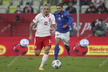 Poland's Kamil Grosicki runs with the ball past Italy's Domenico Berardi during the UEFA Nations League soccer match between Poland and Italy at Energa stadium in Gdansk, Poland