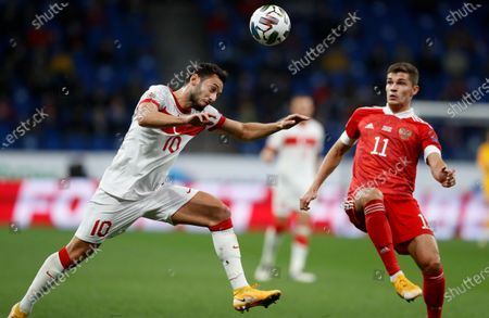 Turkey's Hakan Calhanoglu heads the ball away from Russia's Roman Zobnin, right, during the UEFA Nations League soccer match between Russia and Turkey at Dinamo Stadium in Moscow, Russia
