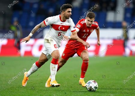 Turkey's Ozan Tufan, left, plays the ball past Russia's Roman Zobnin during the UEFA Nations League soccer match between Russia and Turkey at Dinamo Stadium in Moscow, Russia