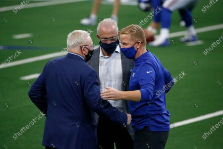 New York Giants offensive coordinator Jason Garrett, right, talks with Dallas Cowboys owner Jerry Jones, left, and chief operating officer Stephen Jones, center, before an NFL football game in Arlington, Texas