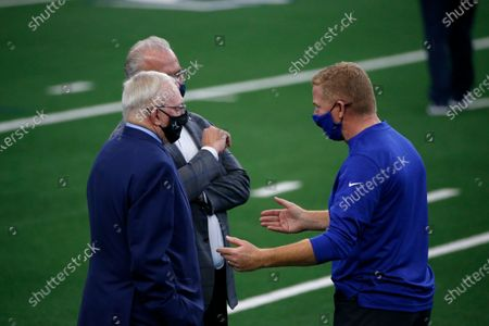 New York Giants offensive coordinator Jason Garrett, right, talks with Dallas Cowboys owner Jerry Jones, front left, and chief operating officer Stephen Jones, back left, before an NFL football game in Arlington, Texas