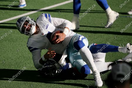 Stock Image of Dallas Cowboys quarterback Dak Prescott (4) is tacked by New York Giants cornerback Logan Ryan, bottom, resulting in an injury to Prescott during the second half of an NFL football game in Arlington, Texas