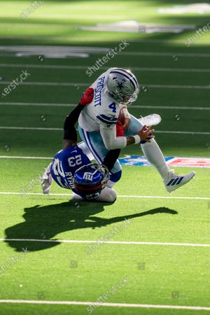 Stock Photo of New York Giants cornerback Logan Ryan (23) tackles Dallas Cowboys quarterback Dak Prescott (4) during an NFL football game, in Arlington, Texas. Prescott would suffer a severe right leg injury on the play and leave the game on the play. Dallas won 37-34