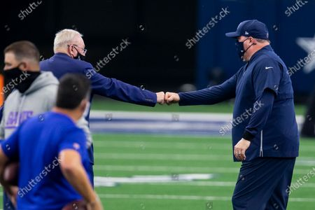 Dallas Cowboys owner Jerry Jones, left, fist bumps head coach Mike McCarthy before an NFL football game against the New York Giants, in Arlington, Texas. Dallas won 37-34