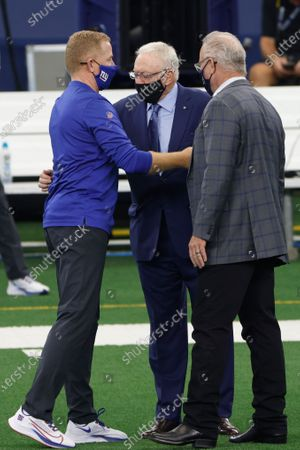 New York Giants offensive coordinator Jason Garrett, left, greets Dallas Cowboys owner Jerry Jones, center, and chief operating officer Stephen Jones, right, before an NFL football game in Arlington, Texas