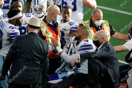 Dallas Cowboys' Joe Thomas (48) and other teammates console quarterback Dak Prescott (4) as he is carted off the field after suffering a leg injury during an NFL football game against the New York Giants in Arlington, Texas