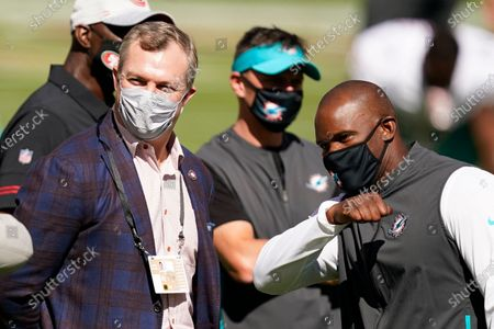 Stock Photo of San Francisco 49ers general manager John Lynch, left, talks with Miami Dolphins head coach Brian Flores before an NFL football game between the 9ers and the Dolphins in Santa Clara, Calif