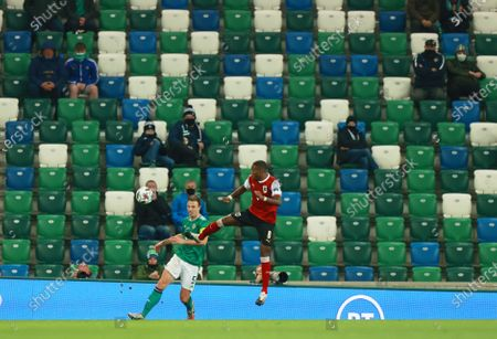 Jonny Evans of Northern Ireland (L) in action against David Alaba of Austria (R) as fans watch the game using social distancing during the UEFA Nations League match between Northern Ireland and Austria in Belfast, Britain, 11 October 2020.