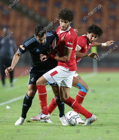 Stock Picture of Al-Ahly player Mohamed Hany (R) and Ahmed Al-Sheikh (C) in action against Pyramids player Abdallah El Said (L) during the Egyptian Premier League soccer match between Al-Ahly and Pyramids at Salam Stadium in Cairo Egypt, 11 October 2020.