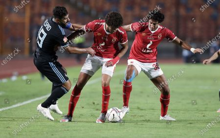 Stock Image of Al-Ahly player Mohamed Hany (R) and Ahmed Al-Sheikh (C) in action against Pyramids player Abdallah El Said (L) during the Egyptian Premier League soccer match between Al-Ahly and Pyramids at Salam Stadium in Cairo Egypt, 11 October 2020.