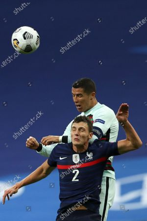 France player Benjamin Pavard (down) fights for the ball with Cristiano Ronaldo of Portugal during the UEFA Nations League soccer match between France and Portugal at Stade de France, Paris, France, 11 October 2020.