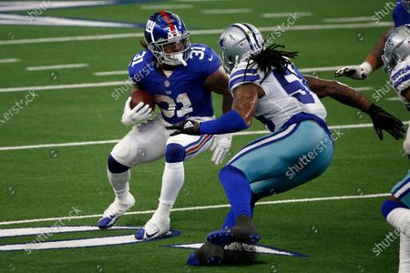 New York Giants running back Devonta Freeman (31) looks for running room as Dallas Cowboys linebacker Jaylon Smith (54) defends in the first half of an NFL football game in Arlington, Texas
