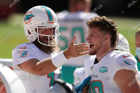 Miami Dolphins quarterback Ryan Fitzpatrick, left, gestures next to wide receiver Adam Shasheen on the sideline during the first half of an NFL football game against the San Francisco 49ers in Santa Clara, Calif
