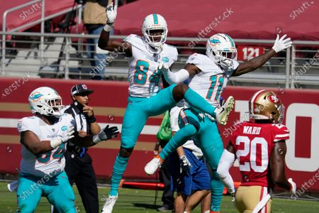 Miami Dolphins wide receiver DeVante Parker (11) celebrates after scoring against the San Francisco 49ers with wide receiver Isaiah Ford (84) and defensive tackle Christian Wilkins (94) during the first half of an NFL football game in Santa Clara, Calif., . Also pictured at right is 49ers free safety Jimmie Ward (20