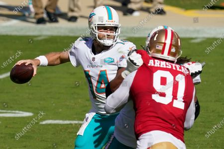 Miami Dolphins quarterback Ryan Fitzpatrick (14) passes as San Francisco 49ers defensive end Arik Armstead (91) applies pressure during the first half of an NFL football game in Santa Clara, Calif