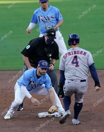 Umpire Chris Conroy watches as Tampa Bay Rays second baseman Brandon Lowe waits to tag out Houston Astros center fielder George Springer on an attempted steal during the third 1 inning in Game 1 of a baseball American League Championship Series, in San Diego