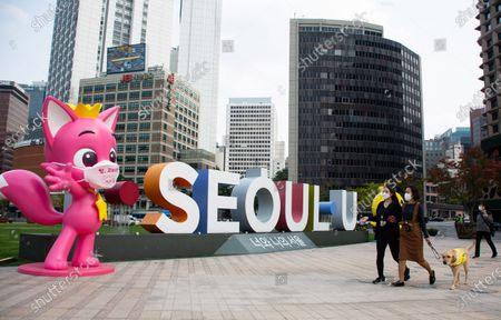 People wearing a masks walk outside Seoul City Hall in Seoul, South Korea, 12 October 2020. The South Korean government decided to lower its social distancing guidelines to the lowest level on 11 October amid a noticeable slowdown in new coronavirus cases.