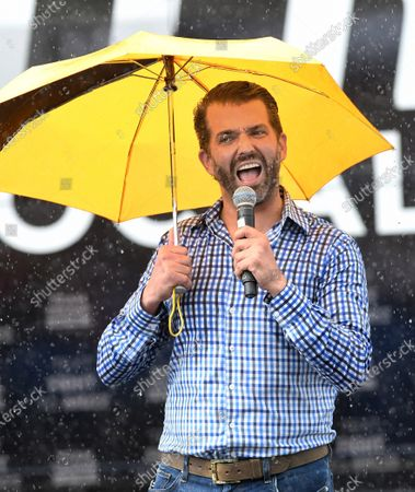 Donald Trump Jr speaks while holding an umbrella during a rain shower at a Fighters Against Socialism campaign rally in support of his father, U.S. President Donald Trump.  UFC fighter Jorge Masvidal also spoke at the event.