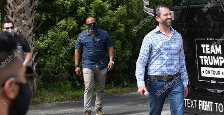 Donald Trump Jr accompanied by three Secret Service agents wearing protective face masks arrives to speak in support of his father, U.S. President Donald Trump, at a Fighters Against Socialism rally, the second of three such events held that day across the state.  UFC fighter Jorge Masvidal also spoke at the event.