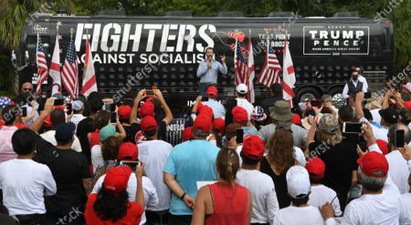 Donald Trump Jr speaks during a rain shower to an audience wearing ponchos at a Fighters Against Socialism campaign rally in support of his father, U.S. President Donald Trump.  UFC fighter Jorge Masvidal also spoke at the event.