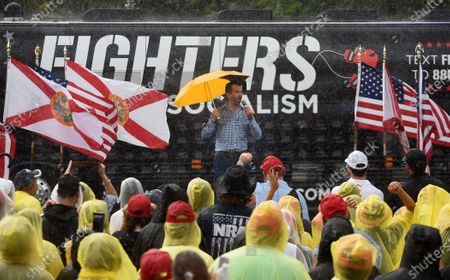 Donald Trump Jr speaks while holding an umbrella to supporters wearing ponchos during a rain shower at a Fighters Against Socialism campaign rally in support of his father, U.S. President Donald Trump.  UFC fighter Jorge Masvidal also spoke at the event.