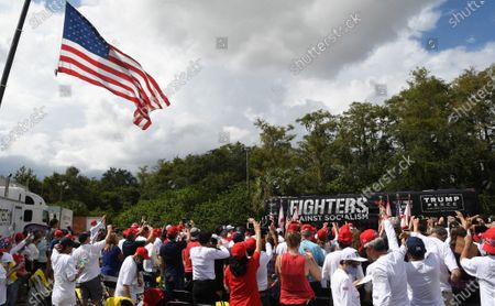 Stock Photo of People react as a bus carrying Donald Trump Jr arrives at a Fighters Against Socialism campaign rally in support of U.S. President Donald Trump.  UFC fighter Jorge Masvidal also spoke at the event.
