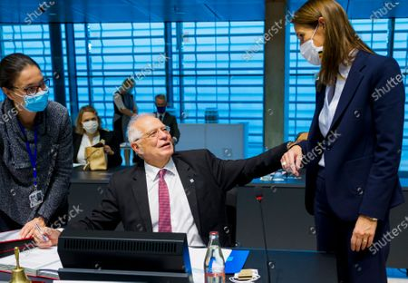 European Union foreign policy chief Josep Borrell, center, speaks with Belgian Foreign Minister Sophie Wilmes, right, during a meeting of European Union foreign ministers at the European Council building in Luxembourg, . European Union foreign ministers were weighing Monday whether to impose sanctions on Russian officials and organizations blamed for the poisoning of opposition leader Alexei Navalny with a Soviet-era nerve agent
