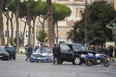 Actors Tom Cruise, center, climbs on to a police car during the shooting of the film Mission Impossible 7, by Christopher McQuarrie, in Rome