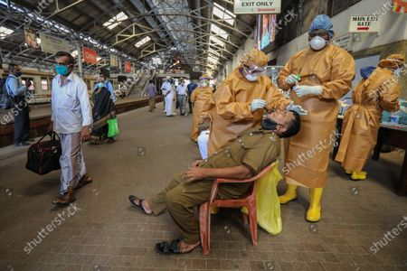 Commuters undergo COVID-19 swab tests at the fort main railway station amid of the coronavirus pandemic in Colombo, Sri Lanka, 12 October 2020. Sri Lankan government implement a curfew in some parts of the country due to a sudden spike of the Covid-19 cluster from a textiles factory in the Gampaha District.