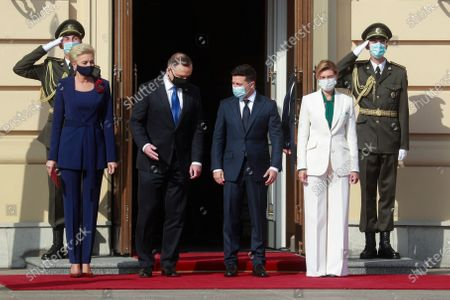 Polish President Andrzej Duda and his wife Agata Kornhauser-Duda, left, and Ukrainian President Volodymyr Zelenskiy and his wife Olena stand together during a welcome ceremony as they meet in Kyiv, Ukraine