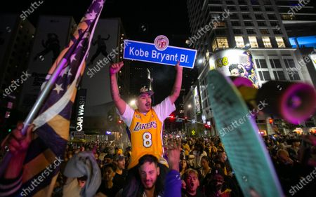 A man holds a Kobe Bryant Bl. sign as fellow fans celebrate of the Lakers 106 - 93 championship win over the Miami Heat on Sunday, Oct. 11, 2020 in Los Angeles, CA. (Jason Armond / Los Angeles Times)