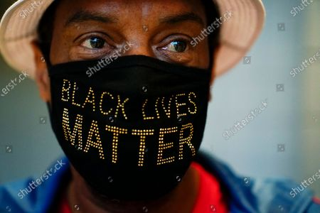 """Stock Photo of Calvin Stalling, of Atlanta wears a """"Black Lives Matter"""" mask while he waits in a line to vote early at the State Farm Arena, in Atlanta"""