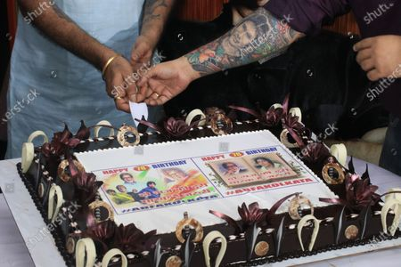 Stock Photo of Member of All Bengal Amitabh Bachchan Fan association slicing cake to celebrate the Indian Actor Amitabh Bachchan 78th  birthday in Kolkata.