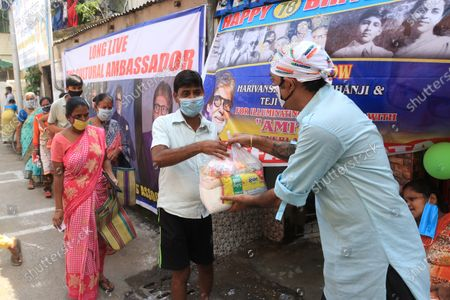 A member of All Bengal Amitabh Bachchan Fan association wearing face mask as precautionary measure against COVID-19 while distributing free food to under privilege during Indian Bollywood actor Amitabh Bachchan 78th birthday in Kolkata.