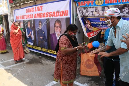 Member of All Bengal Amitabh Bachchan Fan association wearing face mask as precautionary measure against COVID-19 while distributing free food to under privilege during Indian Bollywood actor Amitabh Bachchan 78th birthday in Kolkata.