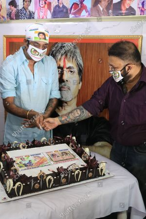 Stock Picture of Member of All Bengal Amitabh Bachchan Fan association slicing cake to celebrate the Indian Actor Amitabh Bachchan 78th  birthday in Kolkata.