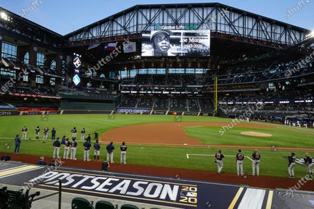 The Atlanta Braves and the Los Angeles Dodgers stand during a moment of silence for Hall of Fame player Joe Morgan, who died Sunday, before Game 1 of a baseball National League Championship Series, in Arlington, Texas