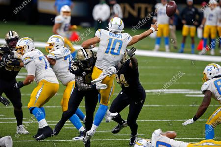 Los Angeles Chargers quarterback Justin Herbert (10) passes under pressure from New Orleans Saints outside linebacker Demario Davis (56) and defensive end Cameron Jordan (94) in the second half of an NFL football game in New Orleans