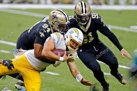 Los Angeles Chargers quarterback Justin Herbert (10) carries as he is tackled by New Orleans Saints defensive end Cameron Jordan (94) and defensive end Trey Hendrickson (91) in the first half of an NFL football game in New Orleans