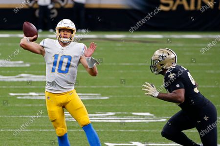 Los Angeles Chargers quarterback Justin Herbert (10) passes under pressure from New Orleans Saints defensive end Cameron Jordan (94) in the first half of an NFL football game in New Orleans
